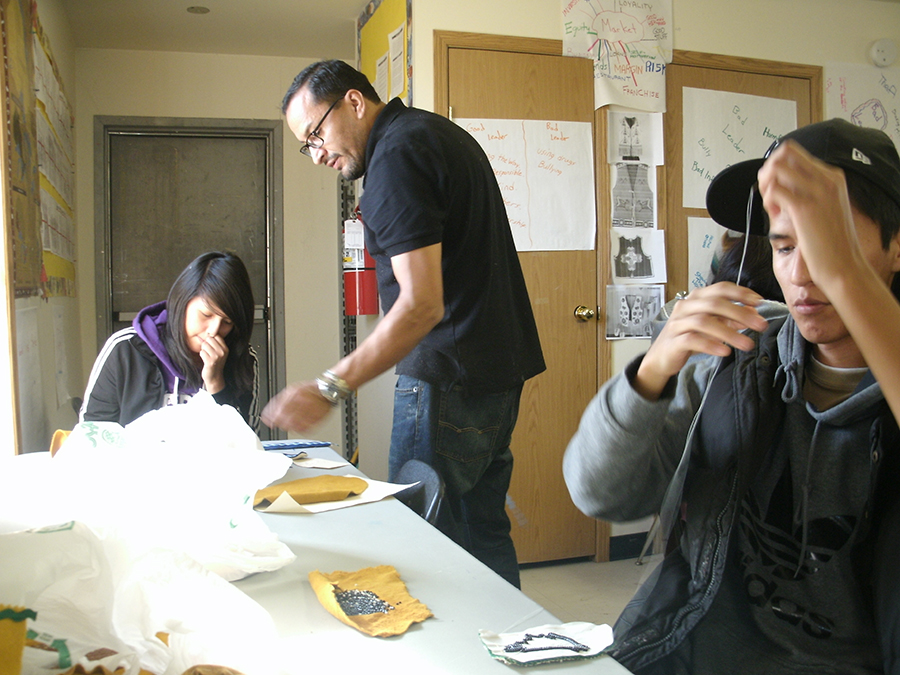 D'arcy Moses, Dene fashion designer, works with Webequie highschool students on making moccasins with a contemporary twist.